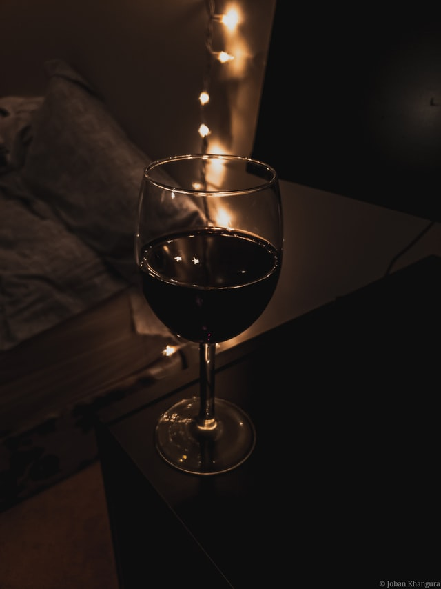 Glass of wine next to bed